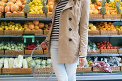 Girl in the supermarket chooses vegetables and fruits. Girl in a beige coat and light blue jeans in the grocery store holding a shopping basket. In the Stock Photos