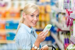 Girl at the supermarket choosing cosmetics Royalty Free Stock Photo