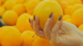 The girl in a supermarket selects the fruit. Woman choosing orange at fruit vegetable supermarket stock video footage