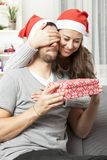 Girl suprise boyfriend with christmas gift. Young happy girl suprise her boyfriend with christmas gift Royalty Free Stock Photo