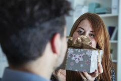 Girl suprise her boyfriend with christmas gift. Young happy girl suprise her boyfriend with christmas gift Royalty Free Stock Photo