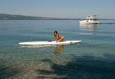 Girl with surf desk and boat. In early morning girl lying on surfing desk in Adriatic sea(Croatia - Dalmatia Stock Photo