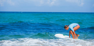 Girl with surf. Teenage girl in blue learning to surf Stock Image
