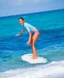 Girl with surf. Teenage girl in blue learning to surf Stock Photography