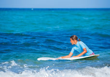 Girl with surf. Teenage girl in blue learning to surf Royalty Free Stock Photo