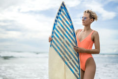 Girl with surfboard on beach Stock Photography