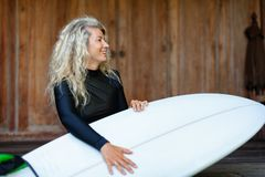 Girl with surfboard sit on veranda steps of beach villa stock photo