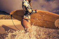 Girl with surfboard In Splashing Wave on a beach. Surfing girl on a beach smiling and ready to go into the water. Vintage postcard style with warm tone and royalty free stock image