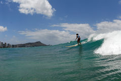 A girl surfer. A girl longboard surfer surfing in Waikiki with Diamond Head in the background Stock Images