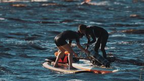 Girl surfers beating each other with soft batons to push opponent into water. Two girl surfers wearing black full swimsuit beating each other with big soft stock video