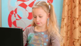 Girl surfing the internet on black laptop computer Stock Photography