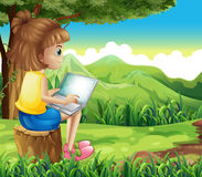A girl surfing the net at the forest Royalty Free Stock Image