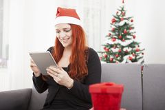 Girl surfing something for christmas on the tablet Royalty Free Stock Photography
