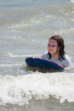 Girl surfing the waves in the ocean on a boogy board Royalty Free Stock Images