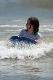 Girl surfing the waves in the ocean on a boogy board Royalty Free Stock Image