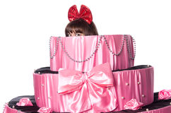 Girl, a surprise gift, looks out a toy cake Royalty Free Stock Photo