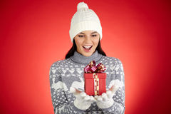 Girl in surprise. Portrait of happy girl in winterwear looking at giftbox on her palms with astonishment royalty free stock photos