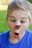 Girl surprised of a butterfly on her nose Stock Photo