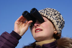 Girl with surprised looks through binoculars Royalty Free Stock Image