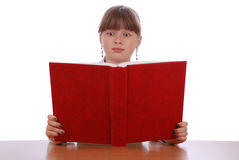 The girl is surprised looks in the red book Royalty Free Stock Photo