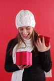 Girl surprised opening gift. Beautiful young girl looking surprised opening a gift Royalty Free Stock Photos