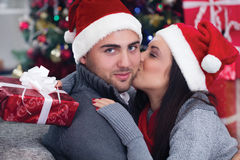 Girl surprising a boy with a gift in Christmas night. A young romantic couple celebrate Christmas night royalty free stock photo