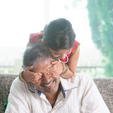 Girl surprising her father by covering daddy eyes Stock Photography