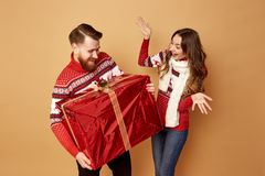 The girl surprisly looks at the guy holding a huge gift. They both are dressed in red and white sweaters with deer stock photo
