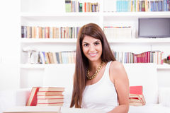 Girl surrounded by books smiling Stock Photography