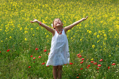 Girl surrounded by rapeseed flowers. Pretty young girl surrounded by rapeseed flowers and lifting her arms up with delight Stock Photo