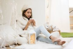 Girl in sweater drink hot tea in house. Beautiful attractive mole woman with white fur hat and sweater drink hot tea or coffee in bedroom at winter with copy royalty free stock photography