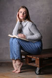 Girl in sweater holding book and sitting on a deck. Gray background Stock Photos