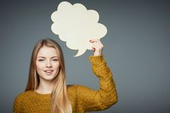 Girl in sweater holding speech bubble smiling royalty free stock images