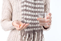 The girl in the sweater keeps before a pill and glass of water close-up Royalty Free Stock Image