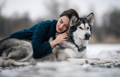 Girl in sweater lies and hugs dog Alaskan Malamute. Girl in sweater hugs a dog Alaskan Malamute. She lies on dog`s back. Her eyes closed Stock Photography