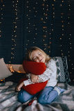 Girl in sweater sitting on bed and hugging red pillow Stock Image