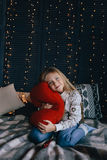 Girl in sweater sitting on bed and hugging red pillow Royalty Free Stock Photo