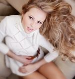 Girl in sweater on the sofa. Beauriful girl in white sweater sitting on the sofa at home Royalty Free Stock Photos