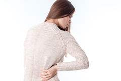 Girl in  sweater stands with his back to the camera keeps  hand on the side of feeling pain is isolated   white backgr Stock Images