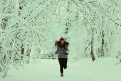 Girl in a sweater in the winter snowy forest Stock Photos
