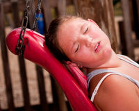 Girl sweats under the hot sun. At playground Royalty Free Stock Photo