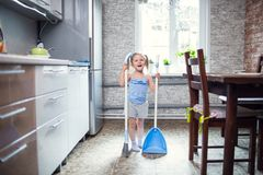 Girl sweeping the floor in the kitchen Stock Photo