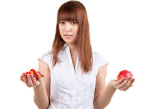 The girl with sweets and an apple. The beautiful girl with sweets and an apple Royalty Free Stock Image