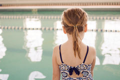 Girl at swim class. A young girl in a blue and white swimsuit fresh out of the pool stares back into the water where she just finished her swim class stock image