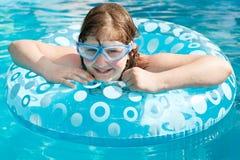 Girl in swim goggle on swimming circle Stock Photos