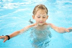 Girl swim in the pool. Little cute girl swim in the pool with blue water Stock Photography