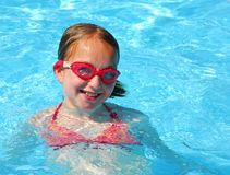 Girl swim pool. Young girl in red goggles in swimming pool Stock Photography