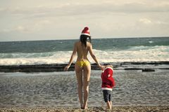 Girl in swim suit and boy wearing santa costume stock images