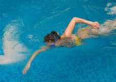 Girl swim in the swimming pool. Athlete girl swim a crawl in the swimming pool Royalty Free Stock Photos