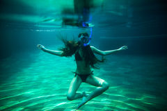 Girl swim underwater pool with snorkel Royalty Free Stock Photos